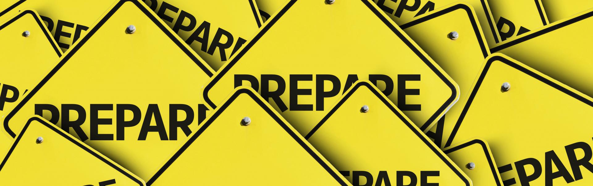 "Yellow signs displaying the word ""prepare"""